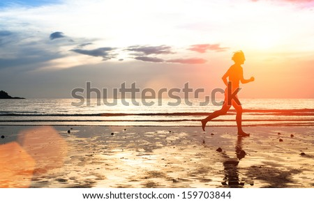 Silhouette of a young woman jogger at sunset on the seashore (with space for text) - stock photo