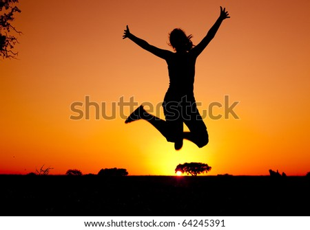 Silhouette of a young woman jumping at the sunset