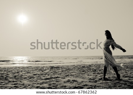 Silhouette of a young woman on a beach walking or dancing in airy white dress blowing in the breeze, back-lit black and white image. - stock photo
