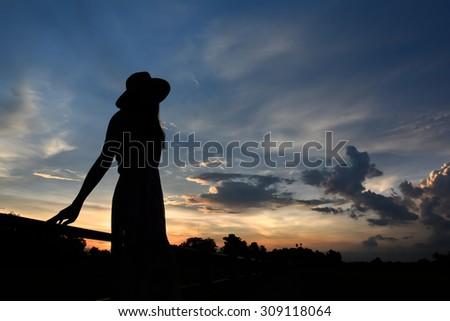 Silhouette of a young woman on the bridge during sunset - stock photo