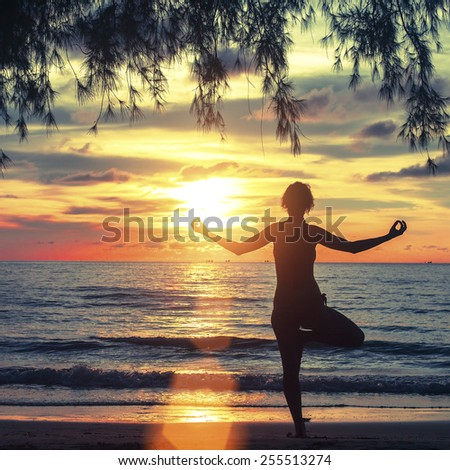 Silhouette of a young woman practicing yoga in the rays of the surrealist sunset at seaside. - stock photo