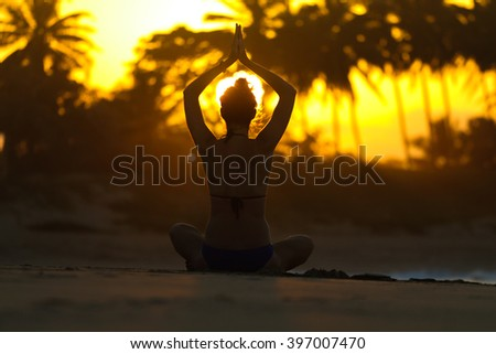 Silhouette of a young woman practicing yoga on the beach at sunset with palm trees on a background