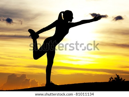 Silhouette of a young woman practicing yoga on the hill against yellow sky with clouds at sunset