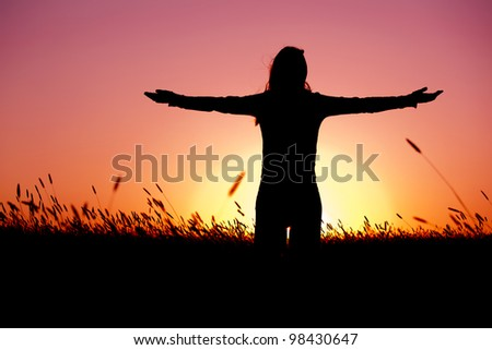 Silhouette of a young woman relaxing on a beautiful sunset of a summer day