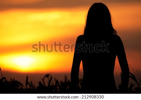 Silhouette of a young woman standing in dry grass field on sunset  - stock photo