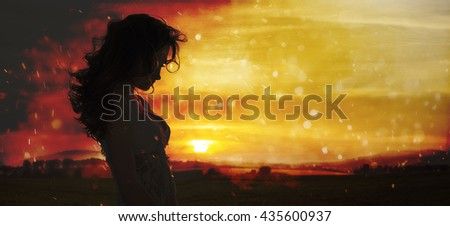 Silhouette of a young woman standing in field on sunset