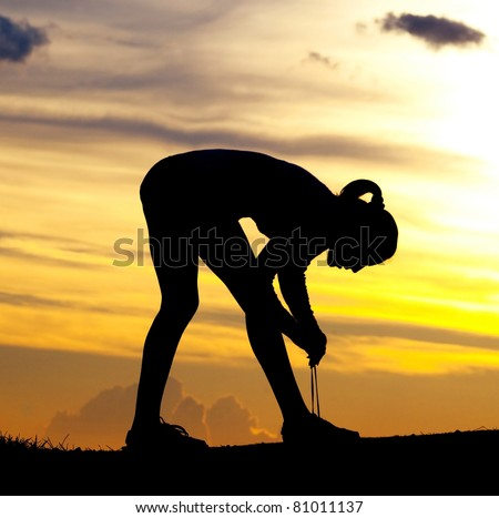Silhouette of a young woman tying shoelaces against yellow sky with clouds at sunset - stock photo