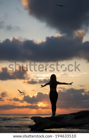 Silhouette of a young woman watching the sunrise