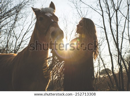 silhouette of a young woman with her horse. concept about animals and people - stock photo