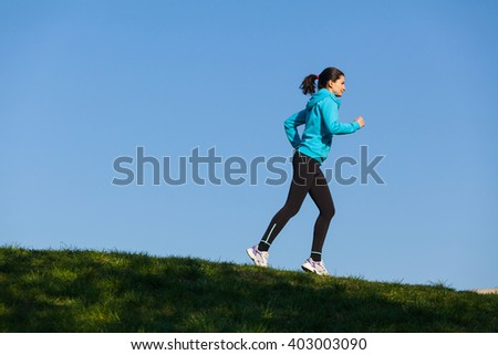 Silhouette of a young woman working out in the park