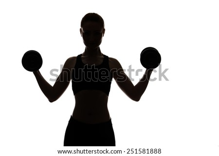 silhouette of a young woman working out lifting dumbbells - stock photo