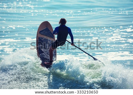 Silhouette of active surfer on paddle board surfing in ocean. - stock photo