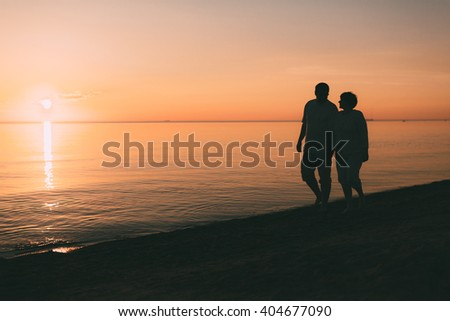 Silhouette of adult couple walks on the seashore against a sunset. Evening photo. - stock photo