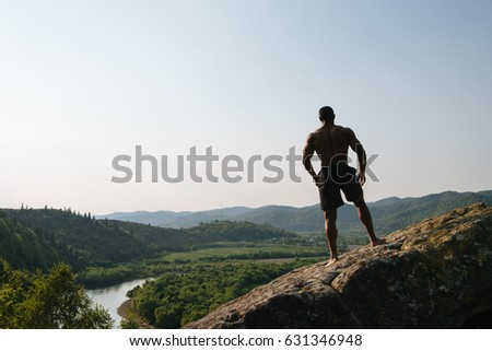 Silhouette of african american athletic man with naked torso posing on the rock. Green mountain nature background