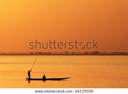 Silhouette of African fisherman in canoe at sunset - stock photo