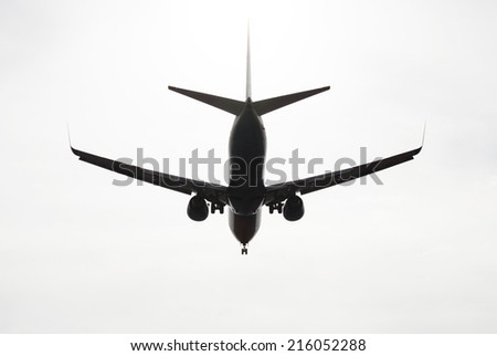 silhouette of aircraft flying in the sky - stock photo