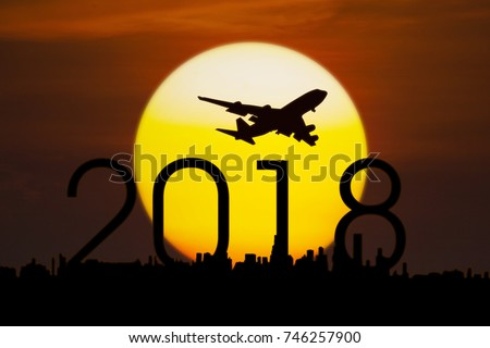 Silhouette of aircraft flying in the sky above numbers 2018 and city with a golden sun, shot at sunset time