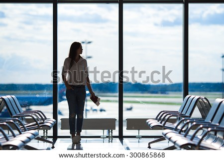 Silhouette of airline passenger in an airport lounge waiting for flight aircraft - stock photo