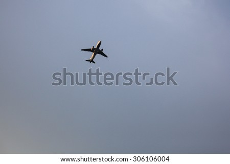 Silhouette of airplane flying in a clear blue sky in the evening. - stock photo