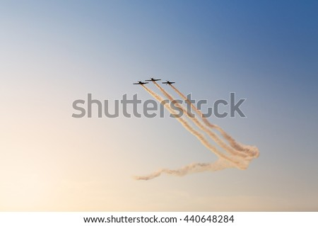 Silhouette of airplanes performing acrobatic flight at sundown. Trace of Smoke behind it - stock photo