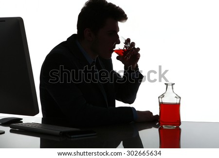 Silhouette of alcoholic drunk man drinking whiskey  / photo of businessman addicted to alcohol at the workplace, depression and crisis concept - stock photo