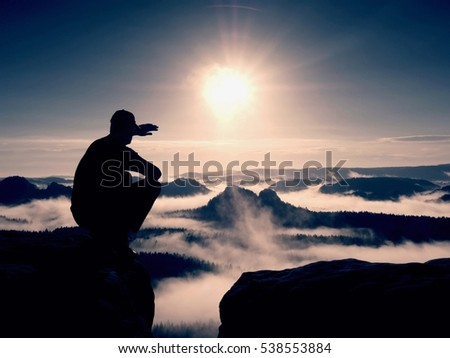 Silhouette of alone hiker in black and cap sit on cliff. Blue filter photo. Man looking to mist bellow. Gentle focus.