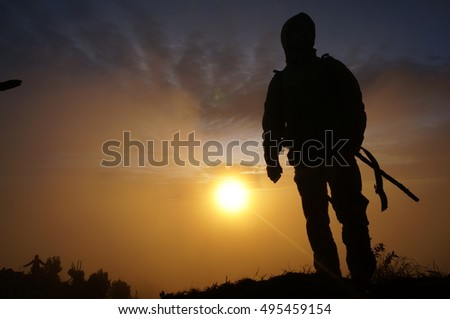 Silhouette of an adventurer on the top of volcanic mountain during sunrise.(reference image fot the other one submit)