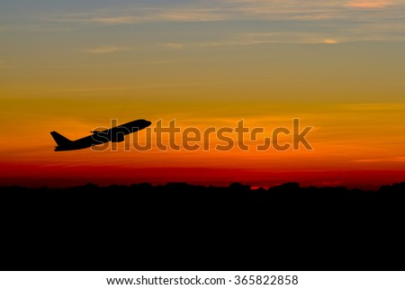 Silhouette of an airplane at sunset. - stock photo