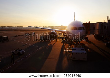 Silhouette of an airplane dock to a disembarkation bridge in an airport against a fiery sunset.