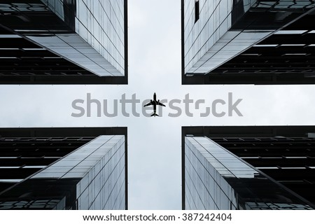 Silhouette of an airplane flying into the crosshair of a symmetrical highrise building.  - stock photo