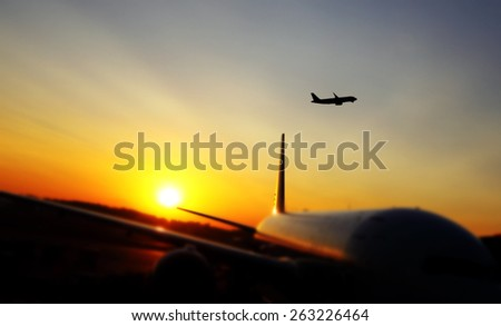 Silhouette of an airplane flying off from an airport runway against a dreamy fiery sunset. - stock photo