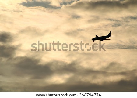 Silhouette of an airplane in the sky against some dramatic clouds.