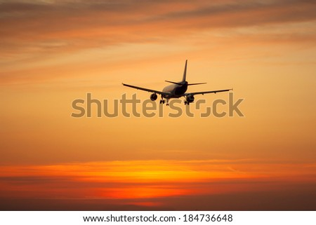 Silhouette of an airplane on sunset background - stock photo