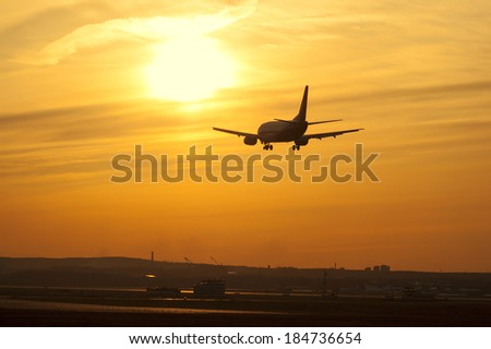 Silhouette of an airplane on sunset background