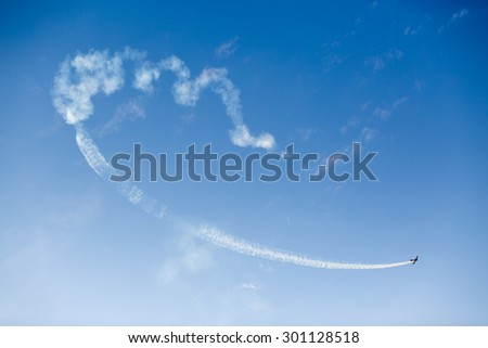 Silhouette of an airplane performing acrobatic flight on blue sky. Trace of Smoke behind - stock photo