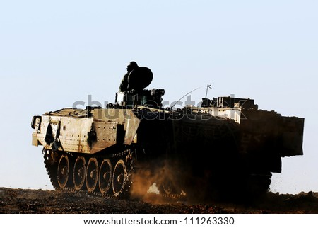 Silhouette of an army soldier on a moving heavily armored personnel carrier. - stock photo