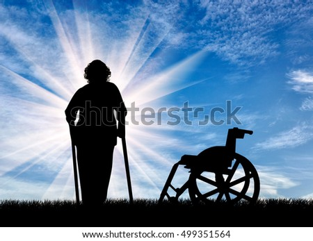 Silhouette of an elderly woman with crutches on background of wheelchair outdoors. Concept of disability and old age