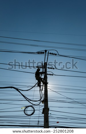 Silhouette of an electrician climbing a newly installed utility pole - stock photo