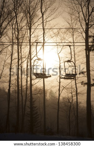 Silhouette of an empty triple ski chairlift against a large rising sun, Stowe, Vermont, USA - stock photo