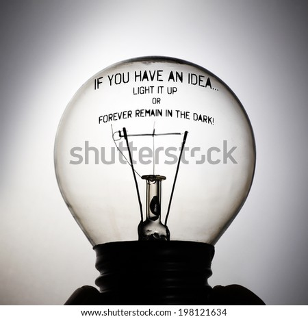 Silhouette of an incandescent light bulb with the message: If you have an idea, light it up or forever remain in the dark! - stock photo