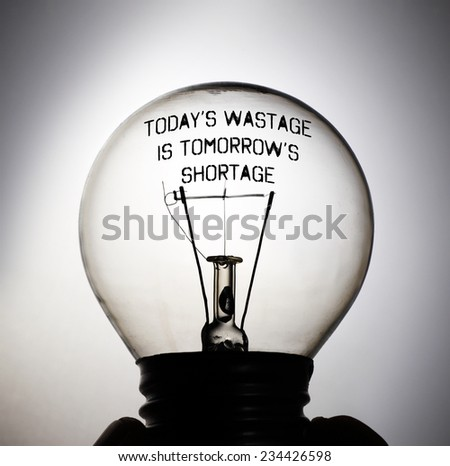 Silhouette of an incandescent light bulb with the message quote: Today's Wastage is Tomorrow's Shortage. - stock photo