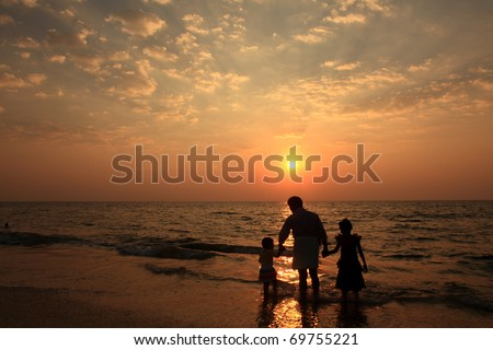 Silhouette of an Indian family enjoying in the beach during sunset - stock photo