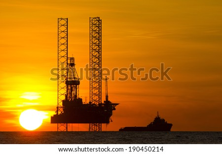 Silhouette of an offshore drilling rig and supply vessel at an orange sunset