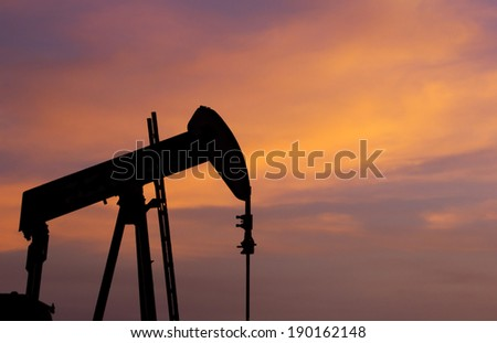 Silhouette of an oil pump at sunset