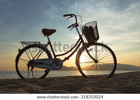 Silhouette of an old bicycle stands on the beach at sunrise - stock photo