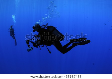 Silhouette of an underwater photographer