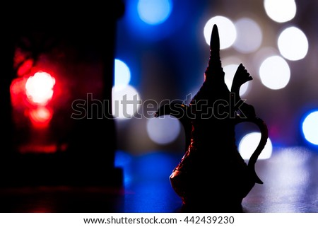 Silhouette of Arabic coffee pot and lantern in out of focus light as background. Ramadan, Eid concept  - stock photo