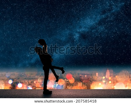 Silhouette of Asian couple, man hold his girlfriend up above the city in night under stars. - stock photo