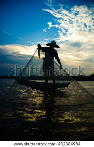 Silhouette of asian fisherman on wooden boat in action casting a net for catching freshwater fish in nature river in the early morning before sunrise - stock photo