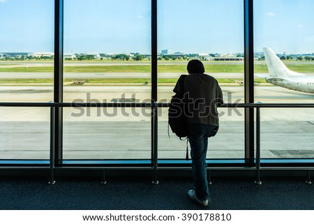 Silhouette of Asian traveler is watching an airplane. He is in the Don Mueang International Airport, Bangkok, Thailand.